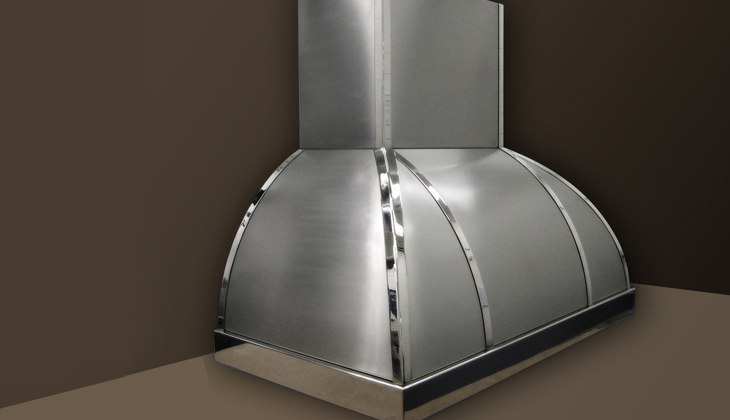Stainless steel wall-mounted kitchen hood. Material number 4 polished with chrome finished trim. Complete fabrication – cut, formed, rolled, corner welded with blending and surface finished.