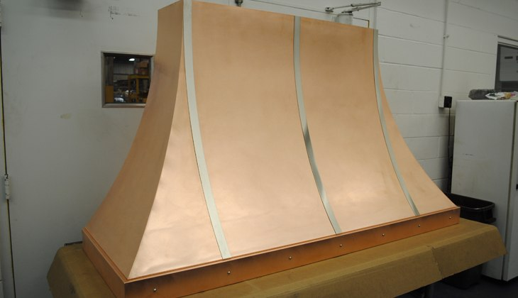 Wall-mounted copper alloy kitchen hood with stainless steel trim and rivets. Complete fabrication – cut, formed, rolled, corner welded with blending and DA finished prior to final antique finish applied.