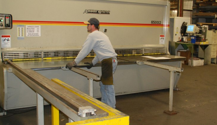 Schebler Specialty Fabrications employee displaying the shearing service, sheet cutting, production shearing and custom shearing options offered by Schebler Specialty Fabrications